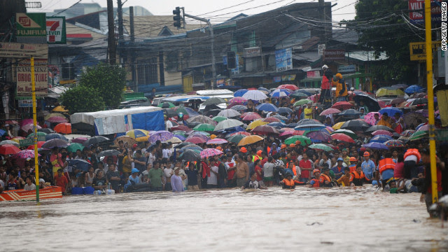 Residents wait for their family members to be rescued at the end of a flooded street in the village of Tumana, a suburb of Manila, Philippines, on Tuesday, August 7.