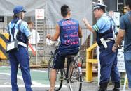 自転車利用者に注意喚起する警察官(10日、東京都世田谷区)
