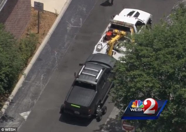 Taken away: The truck that had been carrying Zimmerman is seen near the police station. What appears to be a single bullet hole can be seen in its front passenger seat window