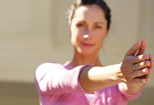 Mulher que faz a ioga, os braços estendidos em frente