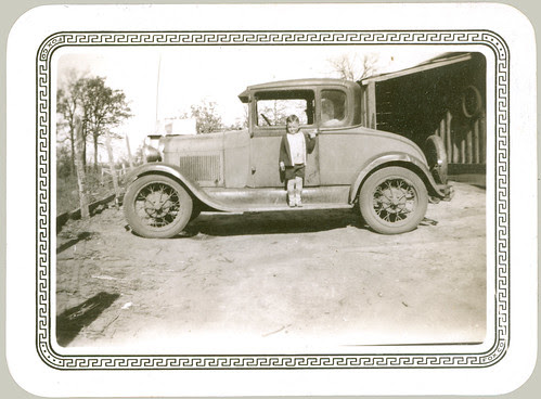 Boy on the running board of coupe.