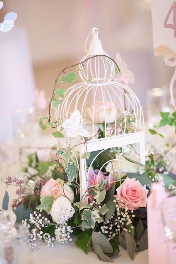ein kleiner weißer Vogelkäfig mit viel grün und mit weißen und rosa Blüten