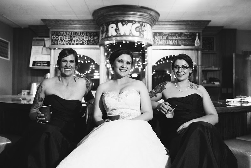 Bride sits with her bridesmaids at old round bar at the Rockford Women's club in downtown Rockford IL.