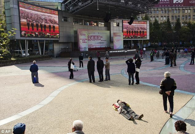 No everyone's interested: A homeless man sleeps on the ground while people watch TV live broadcast of China's new members of the Politburo Standing Committee