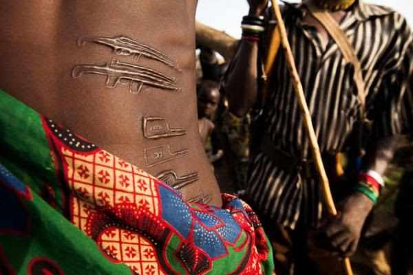 Africa | A warrior with AK-47 scarification marks prepares for battle with a neighboring tribe.  South Sudan, 2012 | ©Trevor Snapp