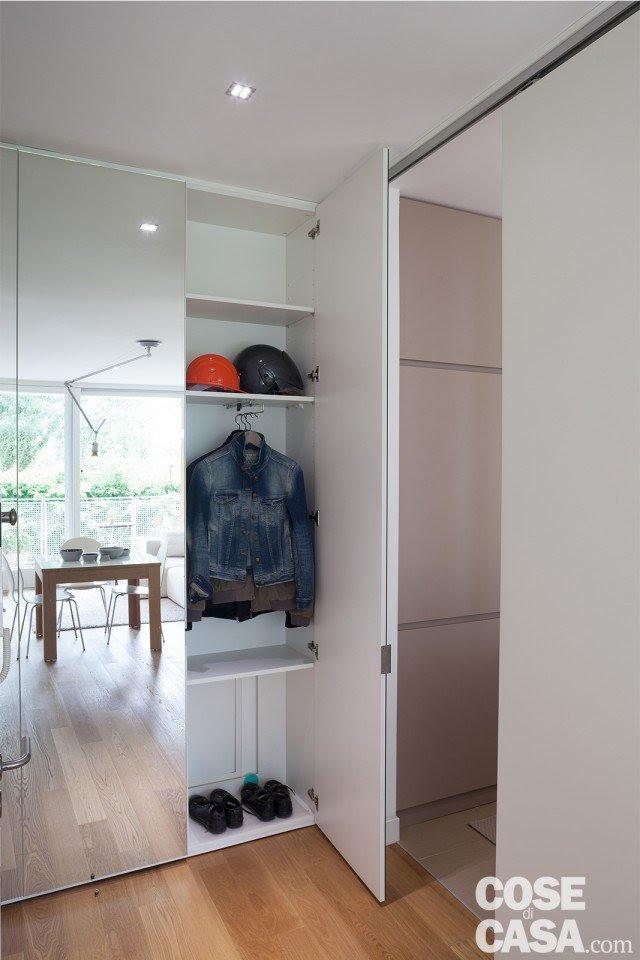 Nell'ingresso una rientranza appena a sinistra della porta ha permesso di inserire un guardaroba su misura per i cappotti e le scarpe, profondo circa 30 cm. L'apertura dell'anta specchiata non interferisce con quella della porta della cucina, che è invece di tipo scorrevole esterno muro.