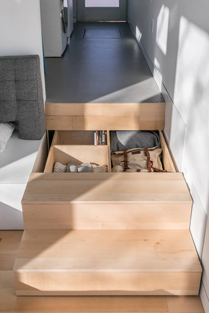 In this modern tiny house, the wooden stairs that lead down to the living room have hidden pull-out storage drawers.