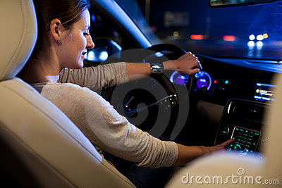 Pretty, young woman driving her modern car