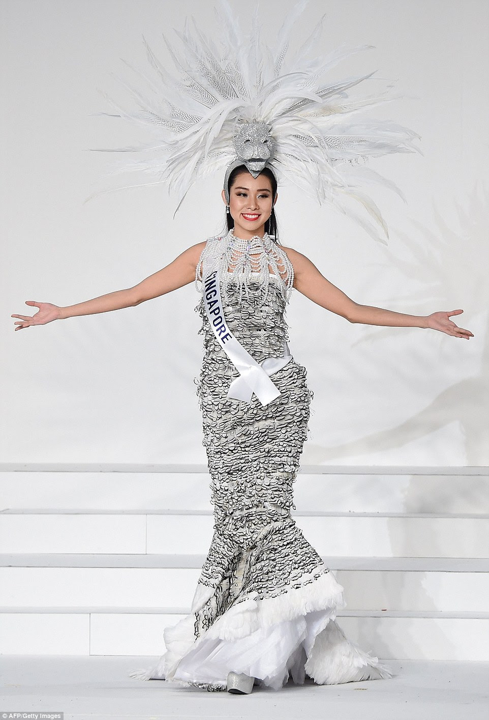 Miss Singapore came dressed as the country's mascot, the half-lion half-fish Merlion. Covered in silver scales, Roxanne Zhang's fish tail breaks into white feathers, which look like a bit like flaked white fish meat, which we guess was the desired effect. Wearing an extravagant pearl necklace, her sparkly lion headdress has a mane of white and black and white striped feathers.