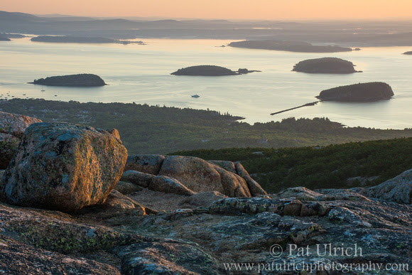 Sunrise illuminates granite boulders on Mount Cadillac in Acadia National Park