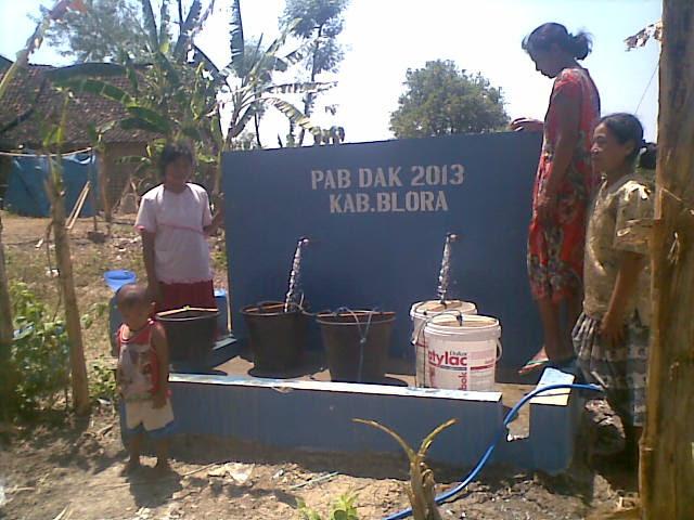 Warga memanfaatkan air dari kran umum