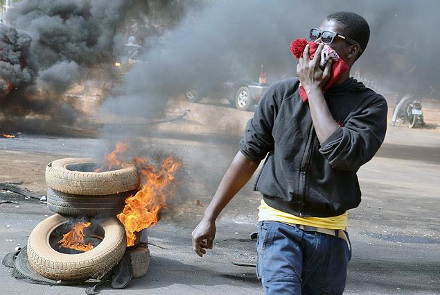 Manifestante queima pneus durante onda de protestos que já deixou dez mortos e destruiu símbolos cristãos no Níger
