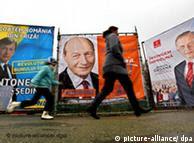 Frau mit Kind geht an Wahlkampfplakaten der Präsidentschaftsgegner Traian Basescu (links) und Mircea Geoana (rechts) in Bukarest vorbei (Foto: dpa)