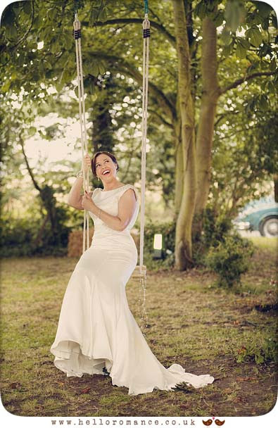 Photo of bride in vintage wedding dress sitting on swing in garden - www.helloromance.co.uk