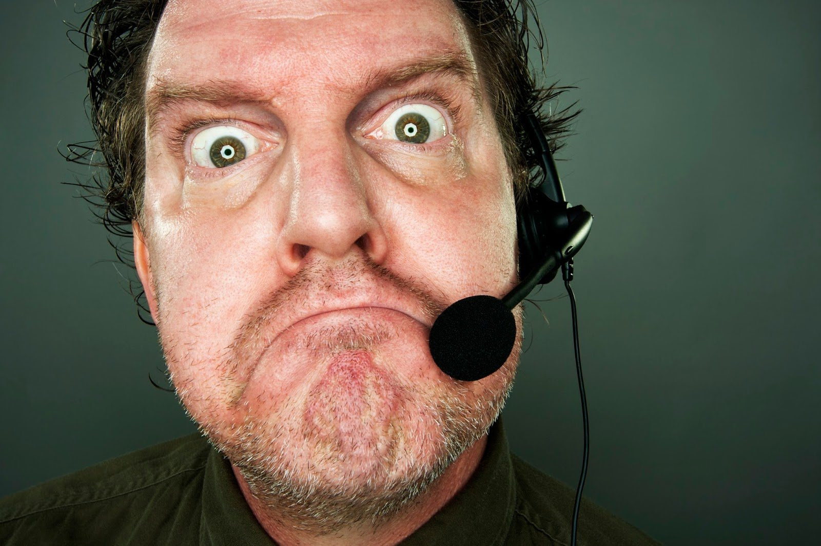 Frowning man with telephone headset.