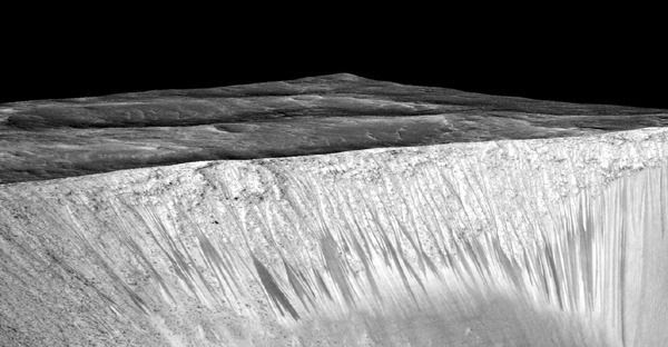 Dark narrow streaks called recurring slope lineae—thought to be formed by the flow of salty liquid water—emanate from the walls of Mars' Garni crater in this image taken by NASA's Mars Reconnaissance Orbiter.