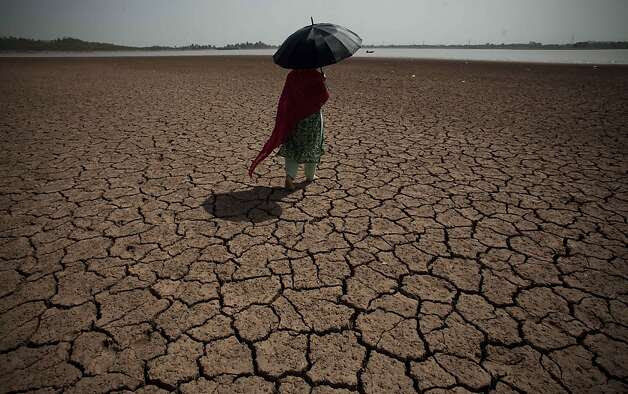 A woman shields herself from the sun as she crosses a parched landscape last year toward a water source that supplies Islamabad and Rawalpindi in Pakistan. Photo: B.K. Bangash, Associated Press