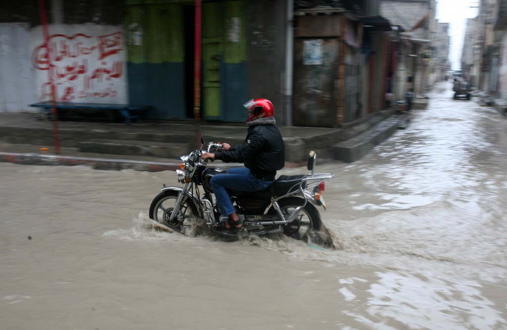 A Palestinian man rides his a bike through a flood in GazaCity. Photo: Mohammed Othman / Flash90