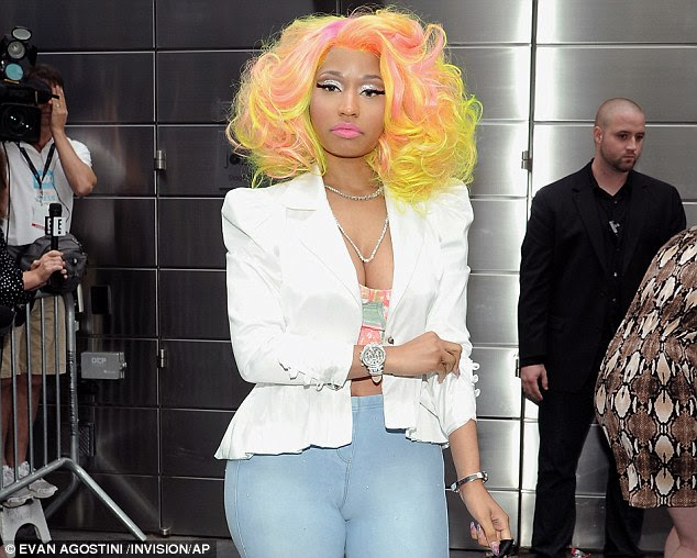 Ready for business: Minaj rolled up her sleeves and flashed her belly and cleavage