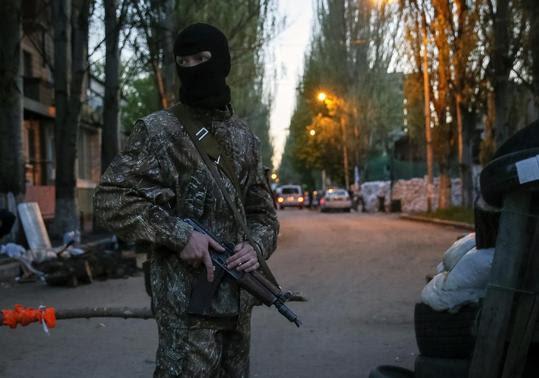 A pro-Russian armed man stands guard at a barricade near the state security service building in Slaviansk, April 25, 2014. REUTERS-Gleb Garanich
