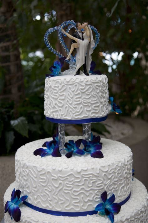 top tier of a royal blue wedding cake decorated with white