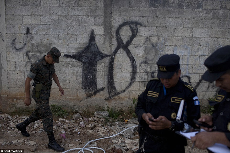 Territory: Authorities pictured in front of graffiti sprayed on a wall by Mara-18 gang members in Guatemala's Zone 6.Some neighbourhoods are controlled by criminal gangs which have walled off their territories