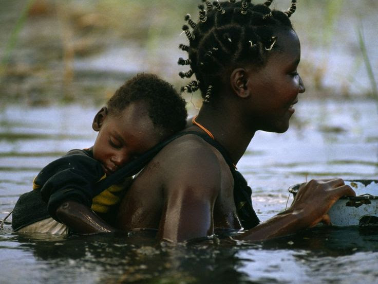 Africa | Sights and Sounds.  Mbukushu mother and child crossing the flooded Okavango River in Botswana