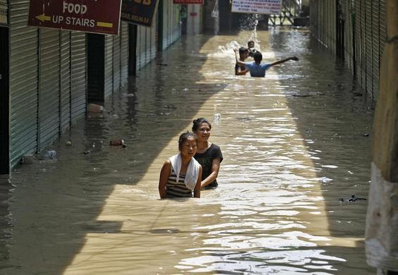 Girls wade through a flooded alley at a shopping arcade after heavy monsoon rains caused the rise in waters of Yamuna river in New Delhi, June 20, 2013. REUTERS-Anindito Mukherjee