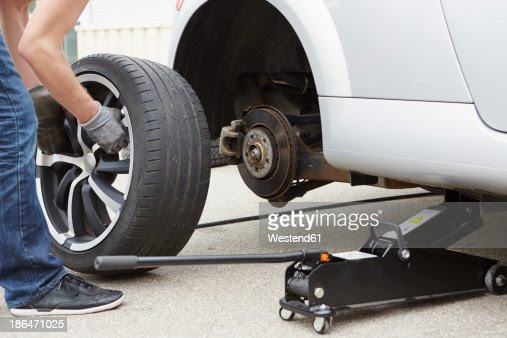 Germany Bavaria Kaufbeuren Mature Man Changing Car Tire