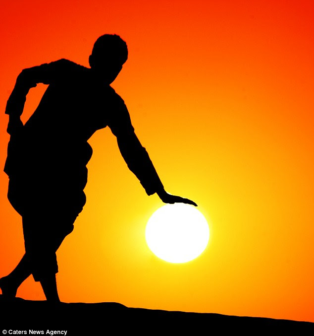 World in his hands: A man look like he is taking as rest on the sun
