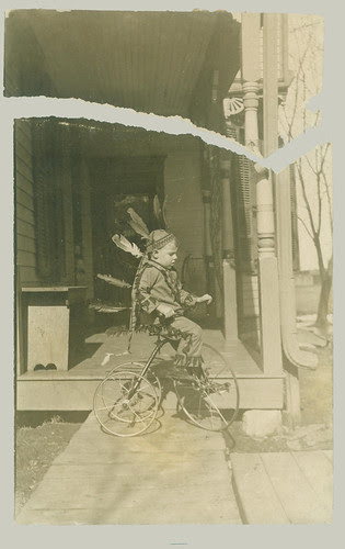Playing in a feathered head dress on a tricycle.