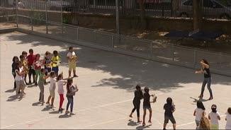Nens ballant en un pati amb una professora