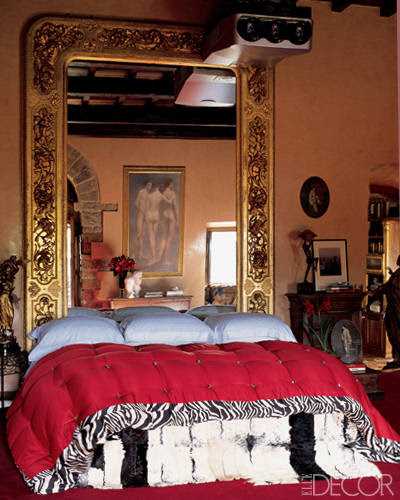 Roberto Cavalli brings his signature opulence and animal prints to the master bedroom of his Tuscan villa. Pieces from Cavalli's extensive art collection are reflected in the 19th-century gilt-wood mirror, which doubles as a headboard. The bed is adorned with a glamorous scarlet and zebra silk duvet cover and a patchwork fur throw—both adding exotic touches.