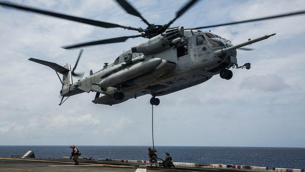 Photo : © USMC - Un CH-53E Super Stallion dépose une cargaison sur un navire.