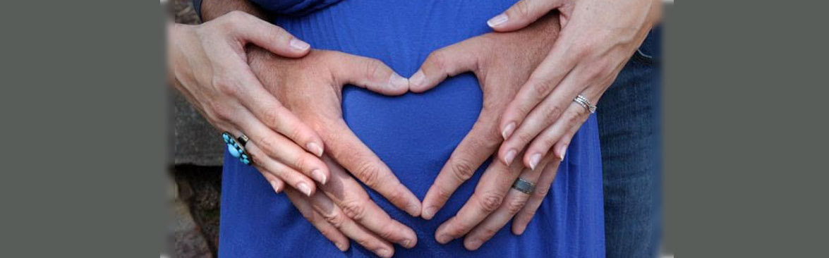 Pregnant woman with her husbands hand in the shape of a heart on her belly.