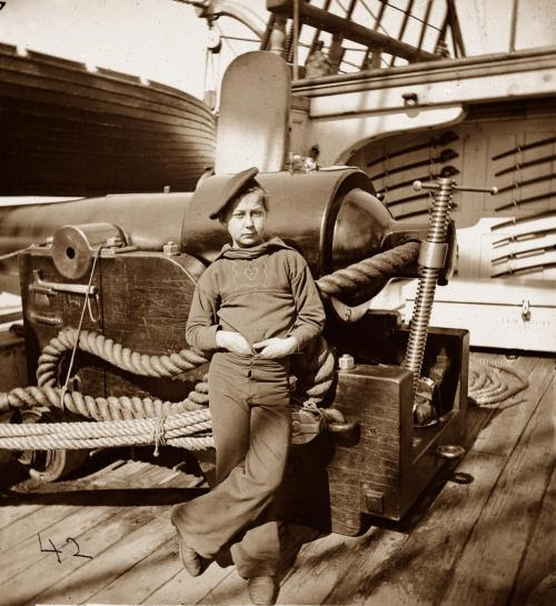 Powder monkey on a Union vessel during the American Civil War. Cutlasses are visible in the background. Circa 1861-1865