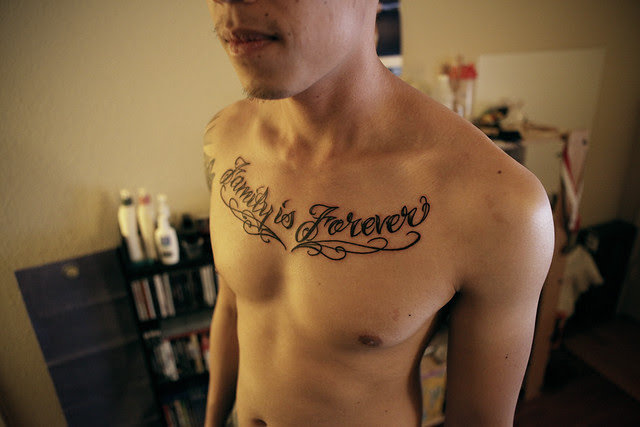 "chest piece tattoo - ""family is forever"". ""family is forever"" in script,"
