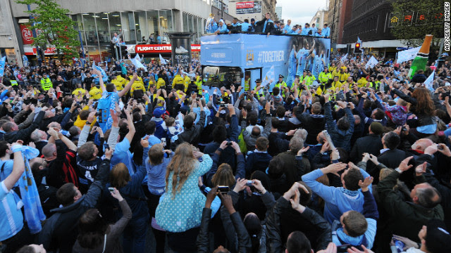 Thousands of supporters crammed the route as the City team paraded the cup on an open top bus through the Manchester city center.