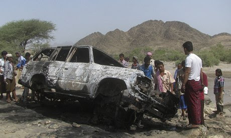 People gather at the site of a drone strike in southern Yemen