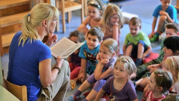 Una maestra leyéndole a unos niños