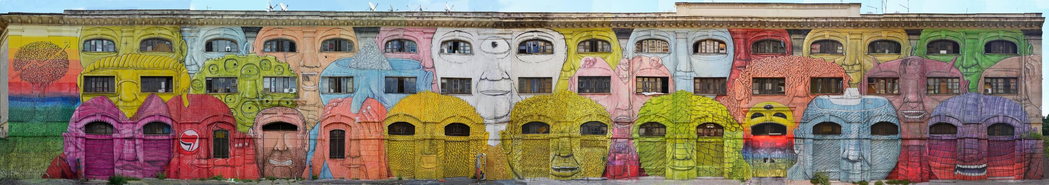 Façana d'uns edificis baixos pintada de manera que semblen cares fent les finestres i portes d'ulls i boques