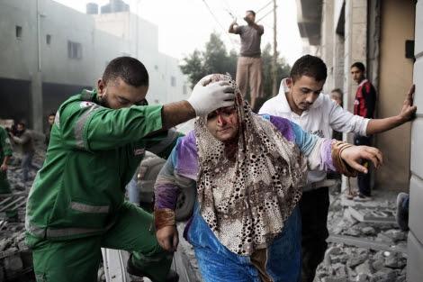 Una mujer palestina es ayudada por un paramédico en Gaza. | Afp