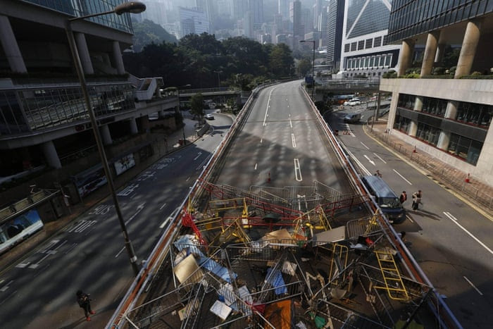 The barricades that were set up by pro-democracy protesters are stockpiled on the main road in Admiralty district, allowing traffic to pass through the heart of Hong Kong for the first time in more than two months
