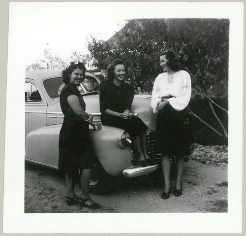 Three women in front of a car