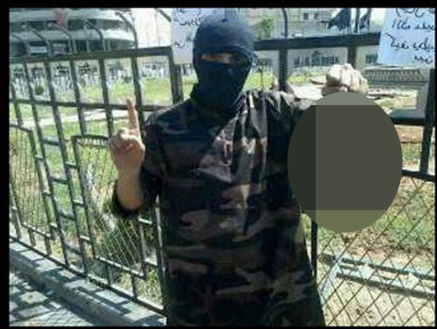 Horrific: The photograph shows masked former rapper Abdel-Majed Abdel Bary, 23, holding the decapitated head while standing in Raqqa's central square