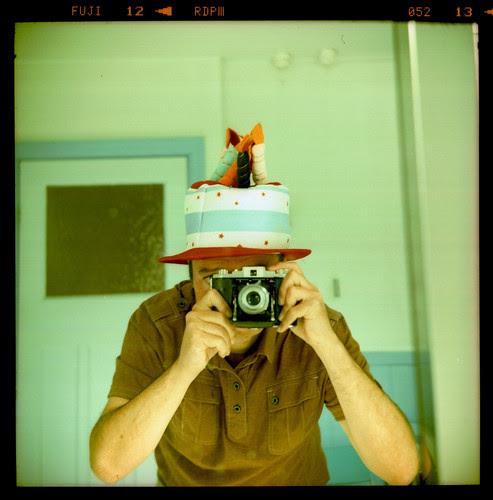reflected self-portrait with Kodak 66 camera and novelty cake hat by pho-Tony