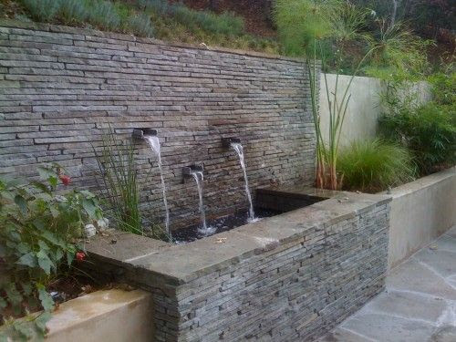 Stone veneer retaining wall by Huettl Landscape Architecture