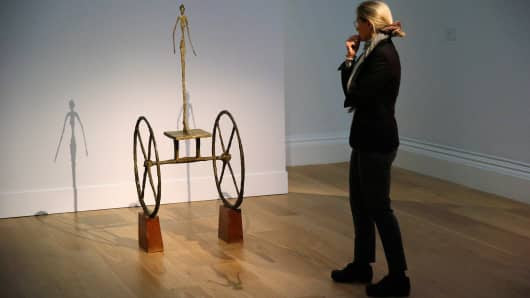 """A visitor looks at """"Chariot"""" by Alberto Giacometti at Sotheby's auction house in London, October 10, 2014."""