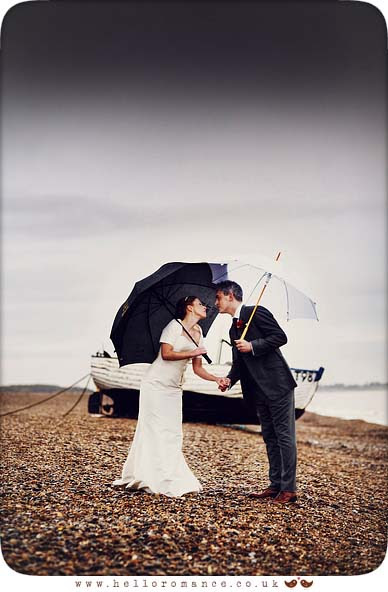 Bride and Groom leaning in for a kiss in rain on Dunwich Beach with umbrellas - Westleton Crown Wedding Photography - Kate and Rob - Hello Romance Wedding Photography Suffolk