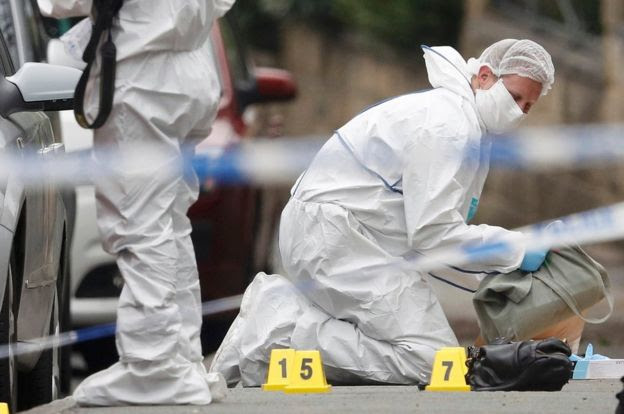 Forensic officers examine objects at the scene